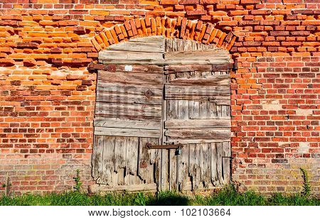 Old wooden closed shutters on the wall from red bricks