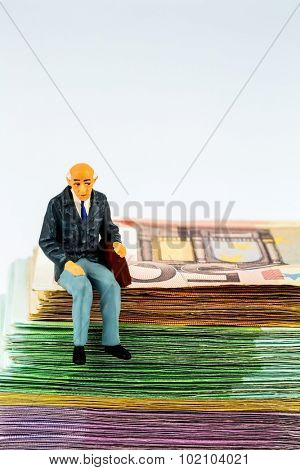 symbolic photo for retirement and old-age security, figure an old man sitting on a stack of bills