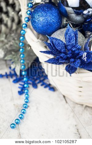 Blue Christmas balls in white wooden basket on white