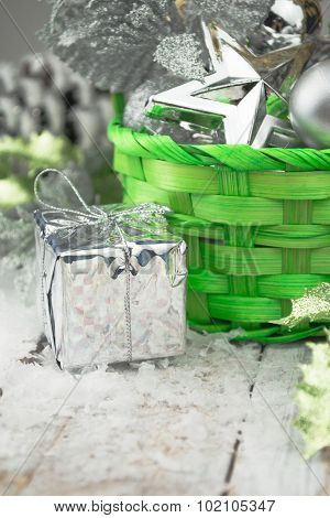 Green Christmas basket with silver toys on a white wooden background