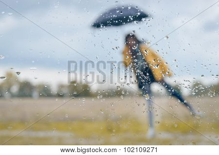 Woman standing under umbrella with raindrops on window glass foreground