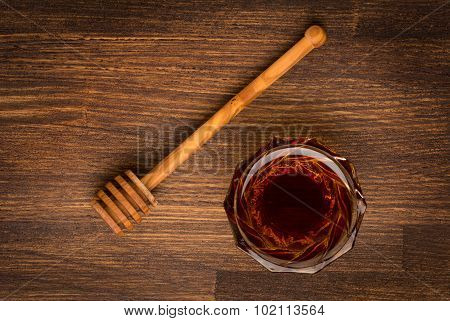 Bowl of honey on wooden table. Aromatic and tasty.
