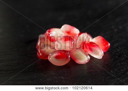 Small Heap Of Pomegranate Seeds On Black Slate Surface
