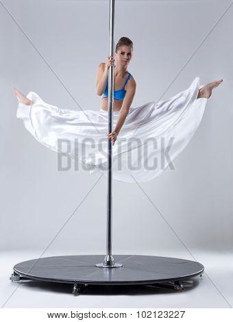 Pole dance. Flexible woman posing in split