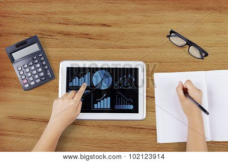 Worker Using Tablet To Analyze Business Charts