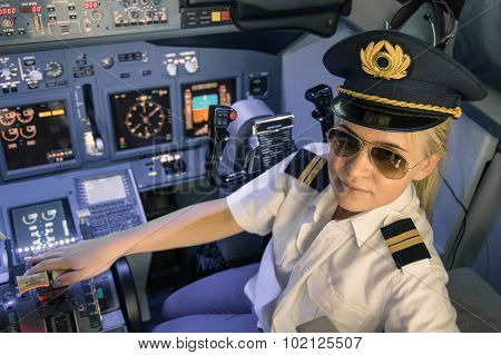 Beautiful Blonde Woman Pilot Wearing Uniform And Hat With Golden Wings - Modern Aircraft Cockpit