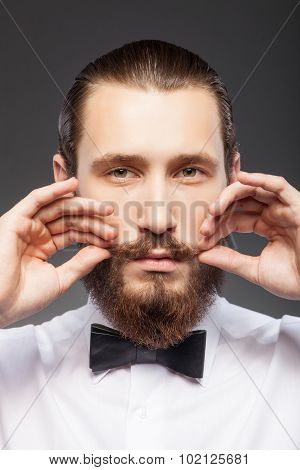 Handsome young bearded guy is caring of his appearance