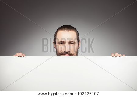 Attractive young bearded hipster guy is advertising something