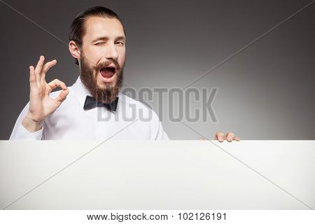 Cheerful young bearded guy is presenting signboard
