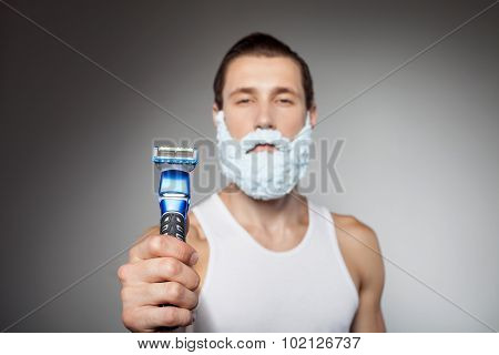 Attractive young bearded man is holding shaver