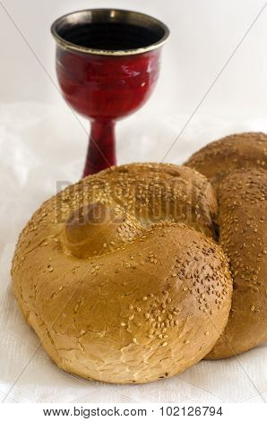 Challah and Wine on white tablecloth for the Jewish weekly ceremonial friday meal to welcome in shabbat.