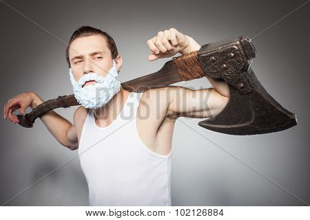 Handsome young hipster guy threatens with axe