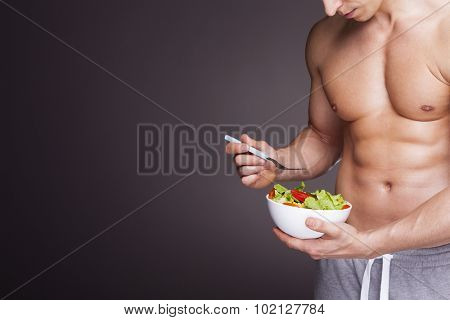 Athletic man holding a bowl of fresh salad on grey background