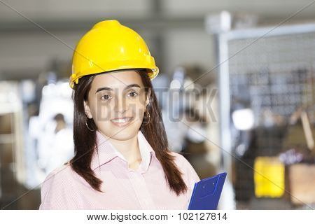 Mechanical engineer standing with a clipboard at metallurgy factory