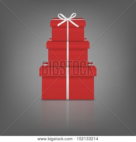 Stack of three realistic red gift boxes with white ribbon and bow