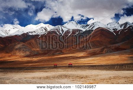 Snow peaks range in Ladakh and valley with two red-roofed pergolas