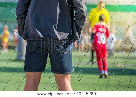 Father Watching Son Playing Soccer Game