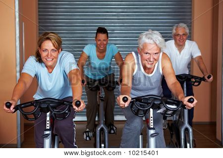 Four People In Fitness Bikes
