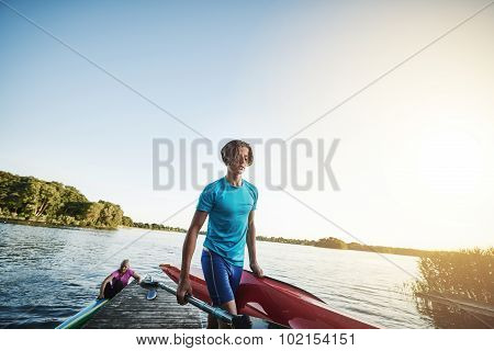 Young Man Carrying A Kayak