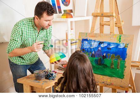 Male Art Teacher Helping A Student