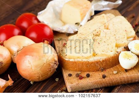 Piece Of Bread With Ripened Cheese On Chopping Board