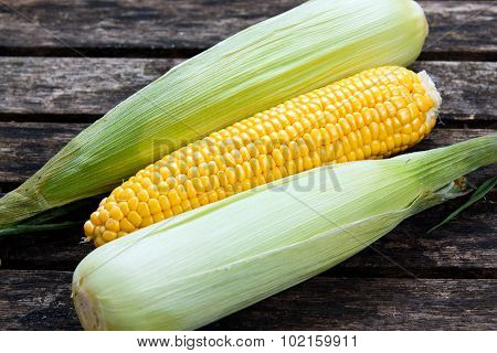 close up Fresh Ripe Sweetcorn on old wooden table. ready to cook