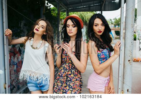 Three beautiful young girls at the bus stop