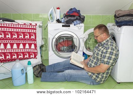 A man washes clothes in the washing machine. Housework men.