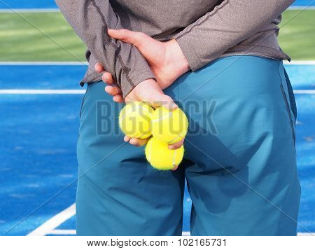 Ball kid holding several Tennis balls behind his back