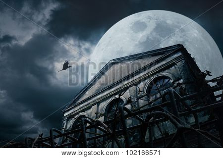 Old Grunge Building With Bird At Night Over Cloudy Sky And The Moon Behind