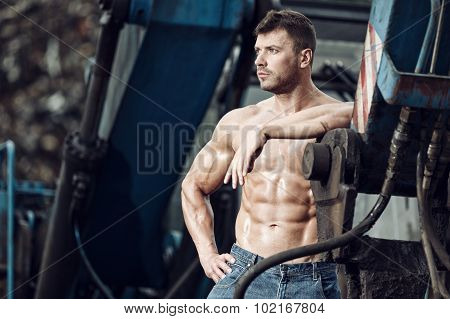 Muscular Man And Heavy Equipment
