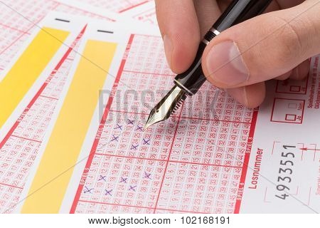Male Hand Filling Lotto Ticket