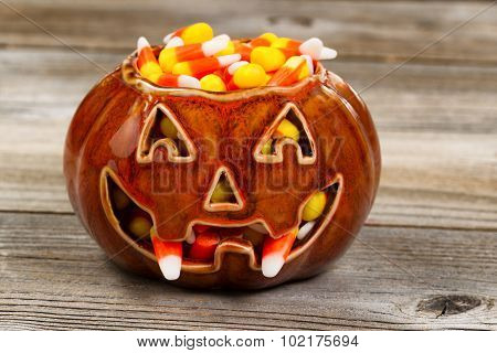 Spooky Fanged Pumpkin Filled With Candy Corn On Rustic Wood
