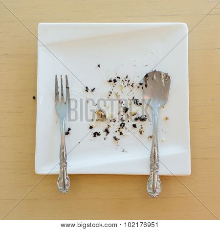 Leftover Of Cake With Fork And Spoon On White Plate