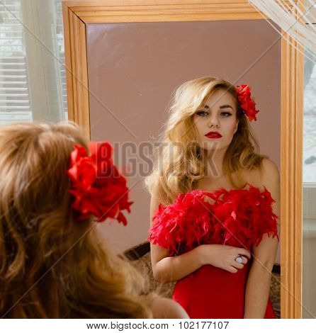 Lady wearing red dress with flower barrette looking in mirror