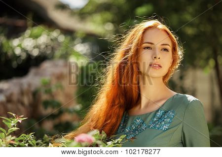 Art portrait of beautiful girl with long red hair