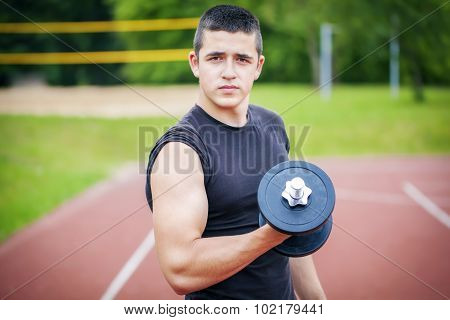 Teenager with dumbbells
