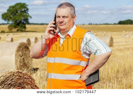 Farmer with smartphone near hay bales on field in summer