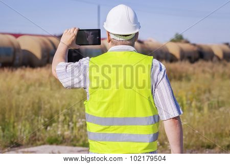Railway Engineer filmed with tablet PC near freight wagons