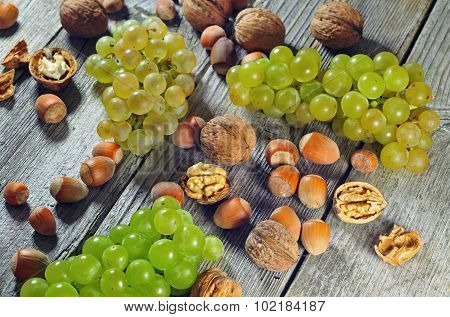 Grapeberries, Hazelnuts And Walnuts On A Wooden Table