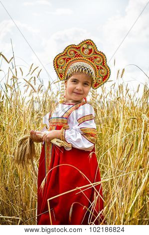 Girl In Russian National A Dress With Ears In Hands Stand In The Field Of The Ripening Wheat