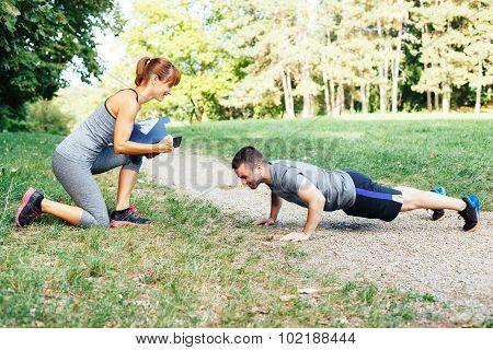 Woman Trainer Motivates Men To Do Push-ups