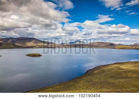 Rhyolitic mountains surround the volcanic lake. Summer travel to Iceland