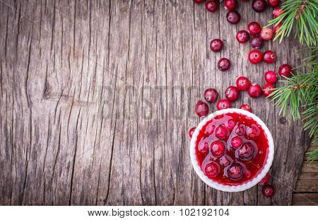 sauce of wild organic cranberries on a wooden table