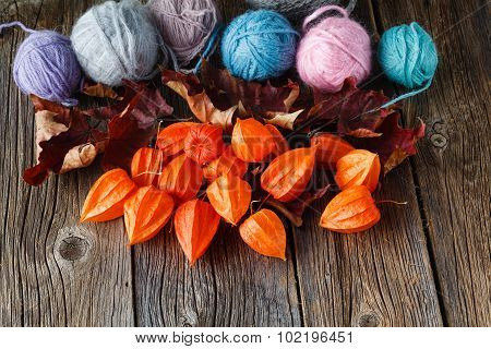 Fall Leaves And Wool Clew  On Rustic Wooden Background