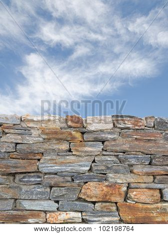 Vertical Background With Rough Stone Wall And Blue Cloudy Sky