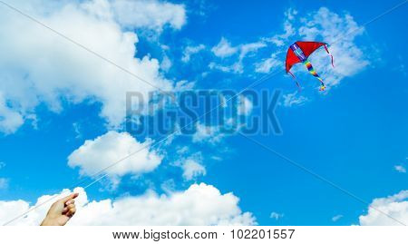Hand holding kite in the cloudy sky. Focus to the kite