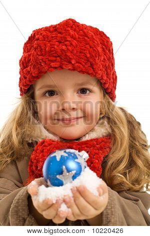 Little Girl With A Handful Of Snow And Christmas Bauble