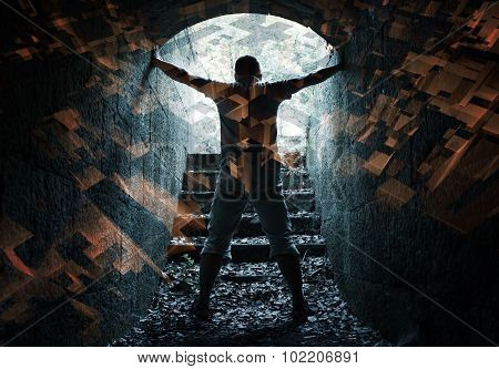 Young Man Stands In Dark Tunnel With Glowing End
