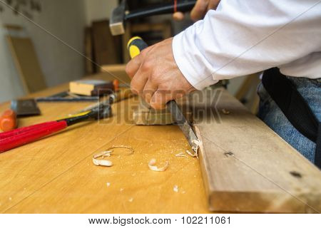 Carpenter Hands In The Foreground With Hammer And Chisel
